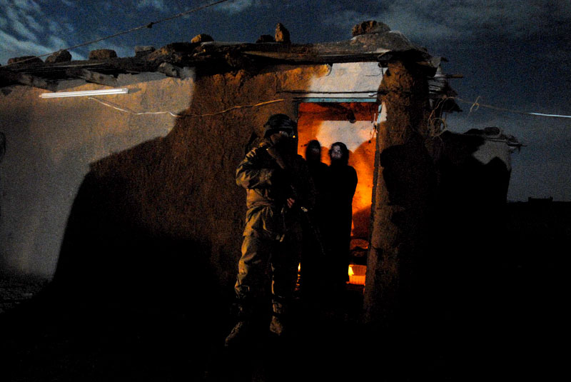 An Iraqi soldier guards a mud hut after a midnight raid on a small farming compound suspected of harboring insurgents.  The hideout was down a long dirt road in the outskirts of Mosul.  It was surrounded by a platoon of Stryker's after midnight on a winter weekend.  The night was bright, the moon full and casting vivid shadows.  The three houses in the compound were raided simultaneously.  A line of soldiers, a 'stack,' moved up discreetly outside each house.  At the signal, the lead soldier kicked in the door and moved out of the way, and the rest of the stack ran behind him with weapons raised and high-powered flashlights scanning rapidly, yelling 'get down' and 'hands up' in English and broken Arabic.  Lining the walls of the hut slept the young family on thin mattresses covered in layers of blankets to keep out the chill of the desert night.  The suspected insurgents sleeping inside had little chance to react.  The man closest to the door was restrained immediately.  He was grabbed and shoved against the wall, a soldier restraining his arms behind his back.  The second man awoke with a start, and immediately started fumbling for something under the blanket.  Hawk, the unit's Kurdish interpreter, took several long steps and punched him sharply in the face, dazing him until he was restrained.  'I should have shot him,' said Hawk, who nevertheless chose not to when given the opportunity.