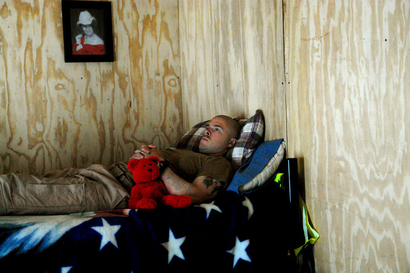 A medic in a helicopter evacuation unit of the 4th Infantry Division (medevacs) rests in his hooch between missions.  His girlfriend in Texas sent the teddy bear to him, and he had another one hanging in the chopper next to his seat. The medevac mission demands long hours of monotony, waiting in small huts next to the helicopters.  When the call comes in on the '9-line' that there are casualties in their sector, the crew scrambles to the 'bird,' usually getting into the air within 10 minutes.  They hurtle to the site of the injury, landing just long enough to take the casualty onboard before flying off to the nearest Combat Support Hospital or Forward Surgical Team.
