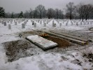 A freshly dug grave is covered by a late winter snow in Section 60 of Arlington National Cemetery.  Section 60 is reserved for the dead from Iraq and Afghanistan, and over 400 fallen soldiers from those conflicts are buried there.  It usually takes a few weeks after burial for the carved marble gravestone to be completed and placed at the grave.  Until then, a small waterproof plastic marker containing the name and rank of the deceased is plunged into the dirt.