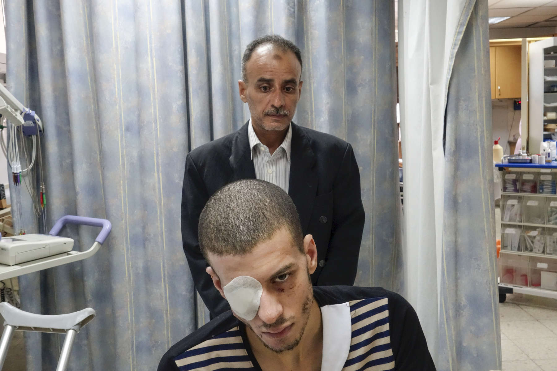 2014. Jerusalem.  Israel. Hassan Al-Hilal, 21 years old.  Imad Al-Hilal, father, 49 years old. From Khan Younis.  Incident on July 22, 2014 at 10pm. He was walking in the street going to buy groceries. His father was 50m behind him when a missile hit. He flew 12m. He is a university student studying software engineering. Burns on the right side of the body. Difficulty moving. Loss of feeling in foot. Shrapnel throughout body. Internal cut in eye. Spent 30 hours in ICU. St Josephs French Hospital in East Jerusalem.   The hospital, owned by the Vatican, was treating the patients pro-bono.  42 had arrived since the beginning of Operation Protective Edge.  3 children have had their limbs amputated. Patients arrived after primary medical treatment. Patients received permits and came through following coordination between Israel, Red Cross, and Red Crescent. Permits are temporary and only for the hospital, meaning they cannot leave the hospital premises.