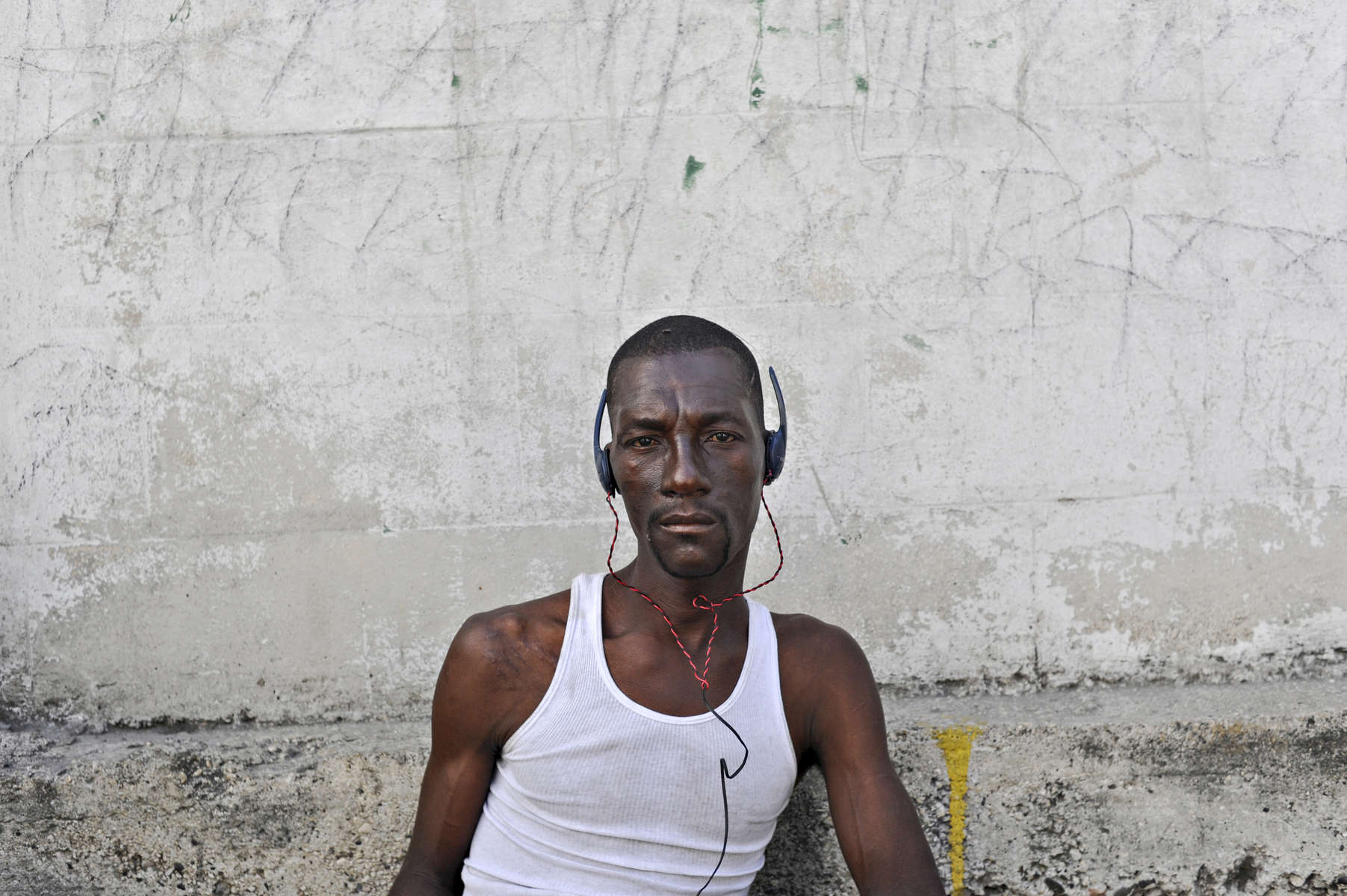 Haiti.  Port-Au-Prince.  2010.  A Haitian worker hired to distribute food aid listens to music while waiting for orders to load his truck with rice.