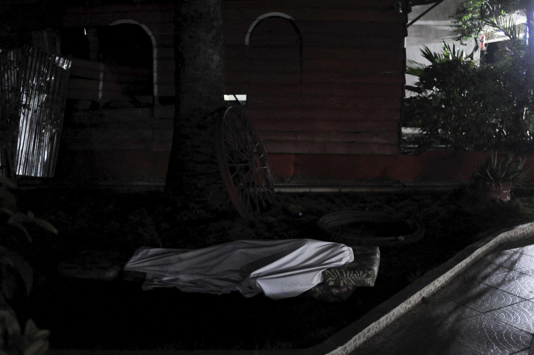 Haiti.  Port-Au-Prince.  2010.  A guest at the Coconut Villa sleeps outside, fearing aftershocks.  Many bodies in the street were also covered in white sheets.