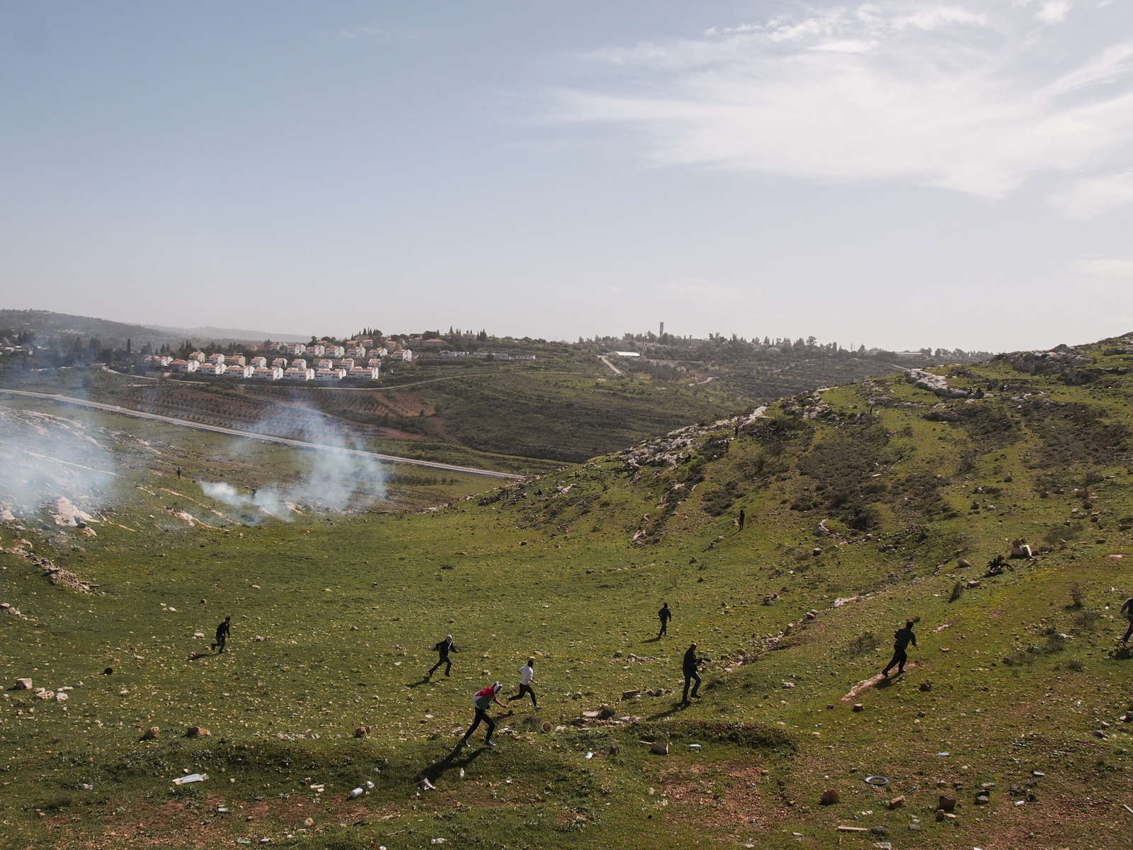 West Bank.  Nabi Saleh.  2013.  Protestors run away as Israeli soldiers fire tear gas at them.  The Israeli settlement of Halimish is in the background. Residents of Nabi Saleh have been protesting the Israeli Occupation every Friday after midday prayers since 2009.  The protests started after Israelis from the nearby settlement of Halimish took over a small spring that had been on Palestinian land.  After widening and adding a bench to the spring, the settlers refused to allow the Palestinians to continue using it.  The weekly protests quickly devolve into rock throwing by the Palestinians and tear gas, rubber bullets, and 'skunk' (a spray mixed with water that has a horrific stench that can linger for weeks) in response by the Israelis.