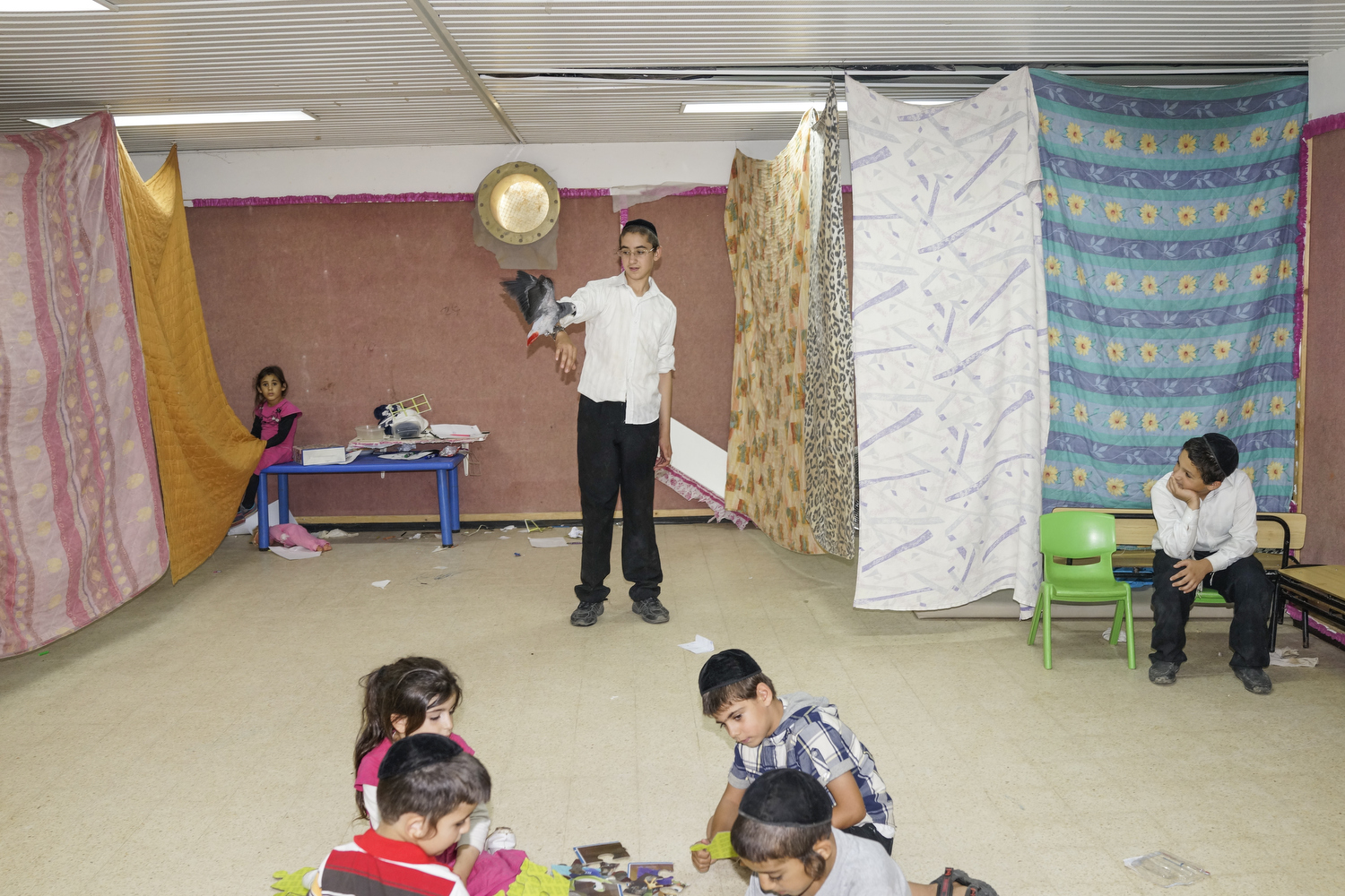 2014.  Netivot.  Israel.  Children in a bomb shelter during Operation Protective Edge.  Since 1991, houses have been mandated to be built with bomb shelters, but in the older neighborhoods communal bomb shelters are still in use.  During the war against Gaza, the elderly and the young often spent their days in the shelters while their parents went to their jobs.