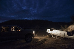 2012.  USA.  Arizona.  Jim Chilton illuminates a destroyed bullet-ridden car on his land.  The car is unconnected to the drug violence to the south, and has been there as a shooting target for years.   Chilton carries a six-shooter and two rifles in his car when traveling through his land.  His 50,000 square acre ranch has 2000 heads of cattle.  Thousands of illegal Mexican immigrants and drug smugglers pass through his land every year.  A small barb wire fence is all that separates his land from Mexico.