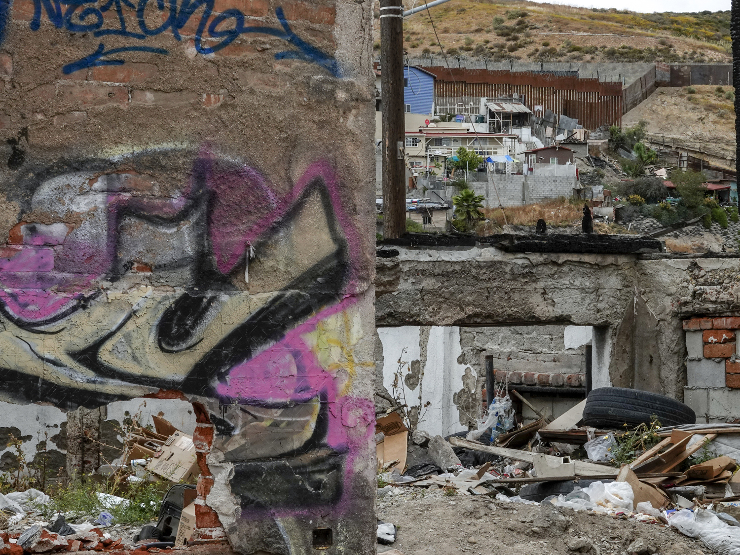 2019. Tijuana. Mexico.  The border wall seen from a destroyed building near Mexico-USA border.