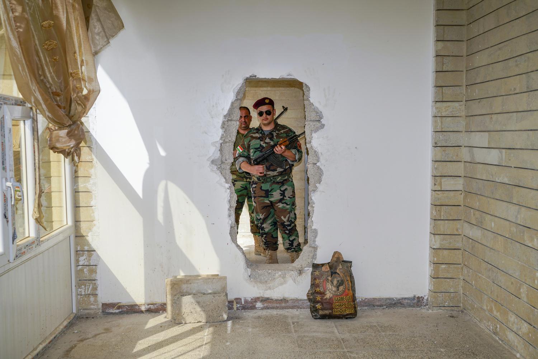 2017. Bashiqa. Iraq. Kurdish Peshmerga pose in ISIS movement holes in a church in Bashiqa.