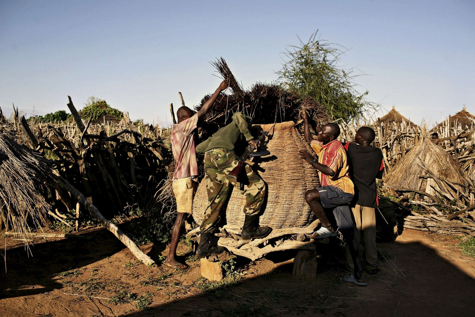 Uganda. Moroto. 2008. Ugandan soldiers search a Karamojang village for illegal weapons.  They found none.