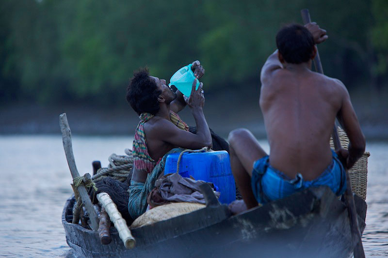 A fisherman in his fishing boat takes a swig of water while his partner paddles.