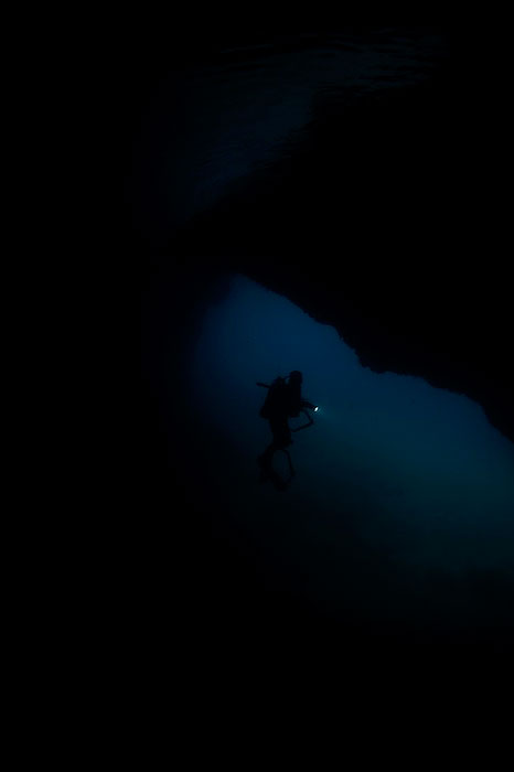 A diver explores a cave in the darkness.