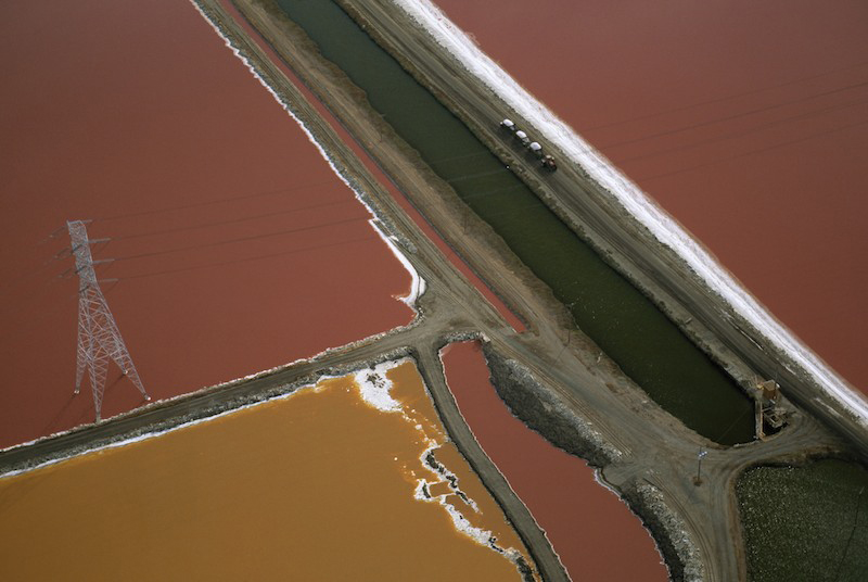 Aerial view of salt ponds with various colors of algae growing in them in the San Francisco Bay area.