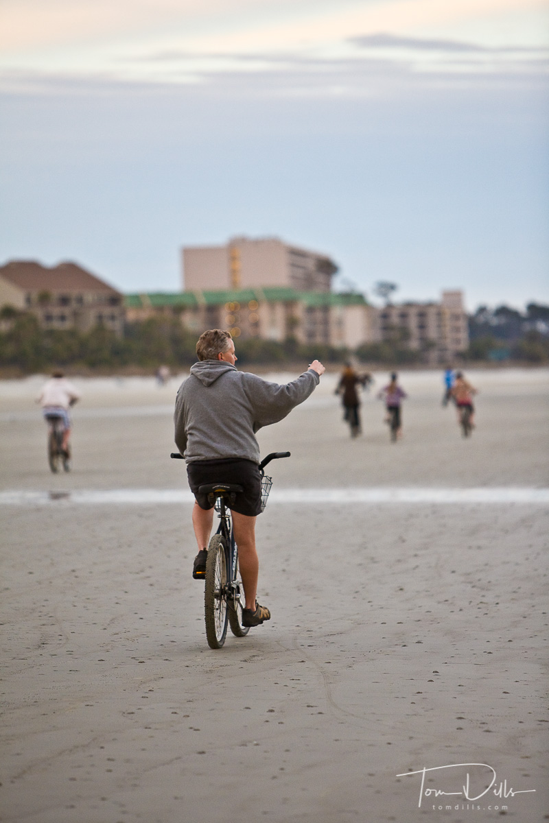 Man riding a bike and taking pictures of dolphins at Hilton Head Island, South Carolina