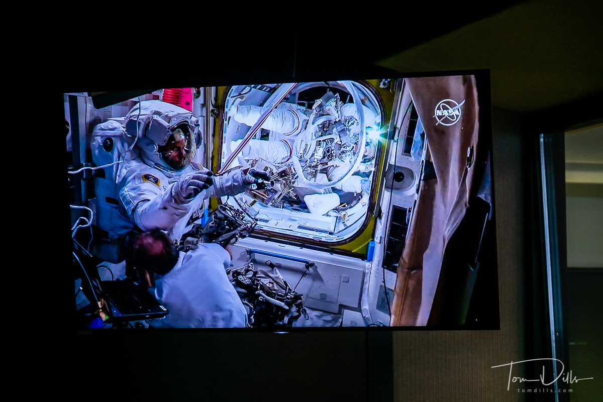 Picture of the TV screen showing live video from the International Space Station of astronauts returning to the ISS from a space walk