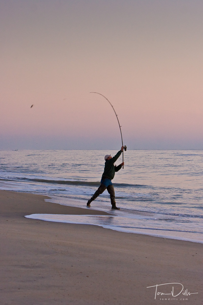 A fisherman casts his line into the surf at Chincoteague Island National Wildlife Refuge, Assateague Island, Virginia