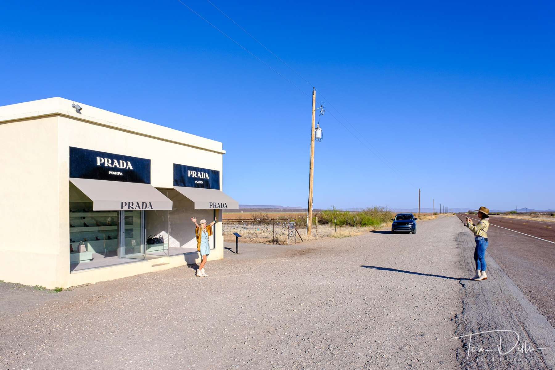 """Prada Marfa is a permanent sculptural art installation by artists Elmgreen and Dragset, located 1.4 miles northwest of Valentine, Texas, just off U.S. Highway 90, and about 26 miles northwest of the city of Marfa.  The installation, in the form of a freestanding building—specifically a Prada storefront—was inaugurated on October 1, 2005. The artists described the work as a {quote}pop architectural land art project."""""""