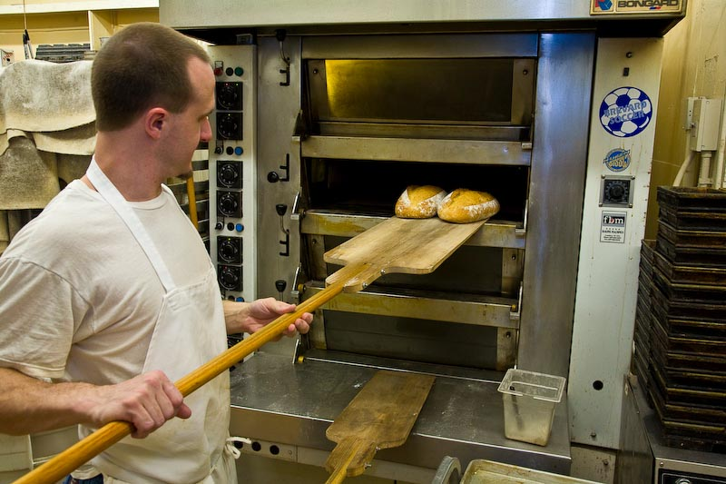 Baker Nick taking fresh baked bread out of the oven at Bracken Mountain Bakery