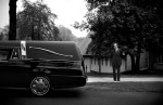 A man gazes at the hearse carrying the remains of a student killed in the shootings after her funeral service.