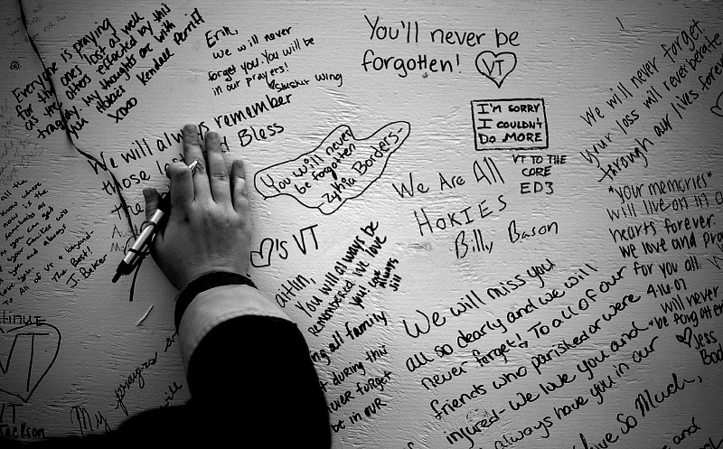 A student pauses before leaving a note of remembrance on one of the wooden boards set up on the drill field across from Norris Hall. The community used these boards as a way to leave notes and pay their respect to those who lost their lives on April 16th.