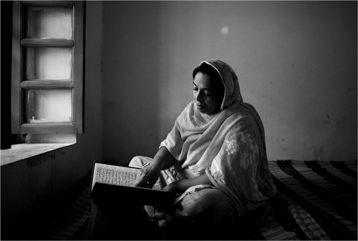 A woman reads by the light of the window in one of the shelter's group bedrooms.