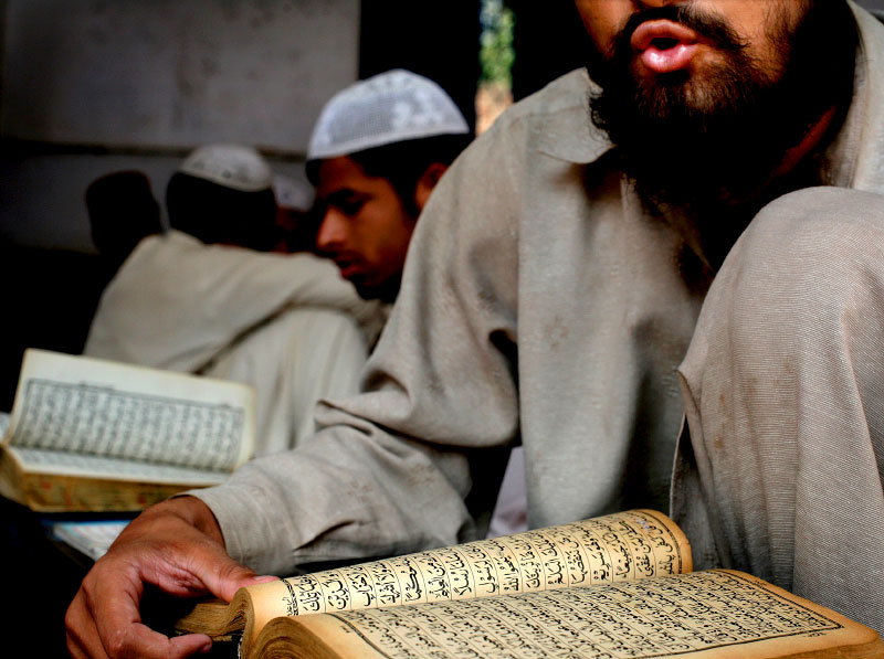 An older student recites lines of the Koran aloud as he participates in his daily studies. It usually takes two to three years to memorize the Koran; and it is believed that once it is memorized, the student is guaranteed an entrance to heaven along with ten people of his choice. The hundreds of pages in the Koran are written in an ancient form of Arabic that is rarely spoken and that the majority of students cannot understand. 