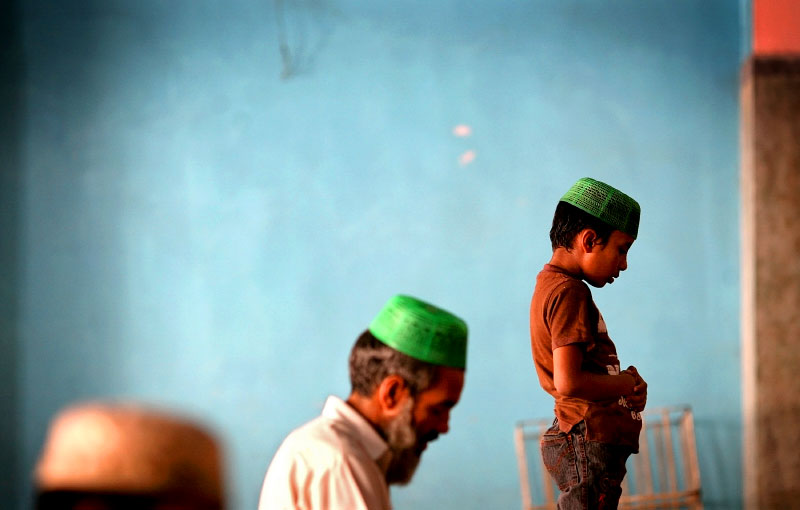 Several generations of Muslim males finish the Dhuhr, or noon prayer, in the mosque of the Jamia Naeemia madrassa. Students at madrassas must strictly observe the five daily prayers.