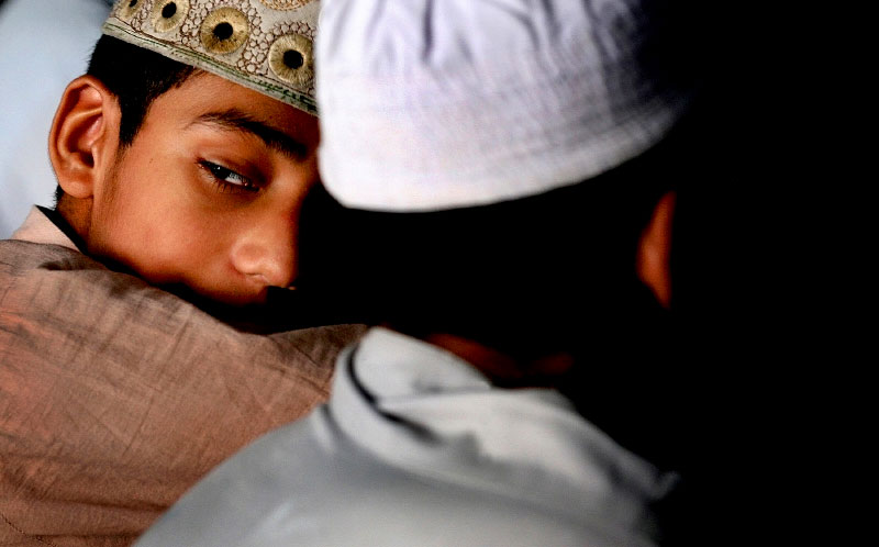 A student peers over his shoulder as he sits in the mosque of the Jamia Naeemia madrassa during an afternoon prayer.