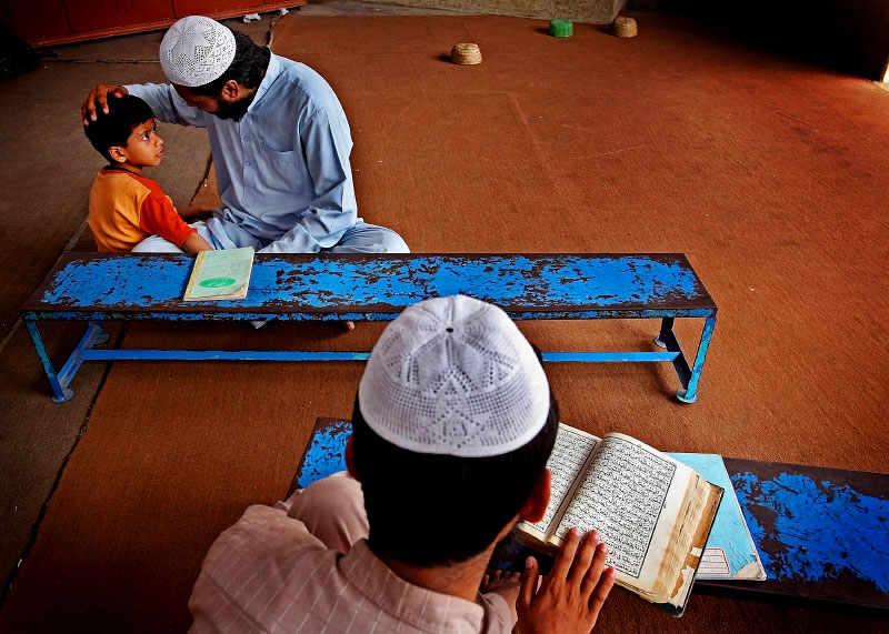 A child learns from an older student as they study at the Jamia Naeemia madrassa. While living away from their parents, many of the children who attend madrassa look up to and learn from the older students, who have spent most of their childhood there as well.