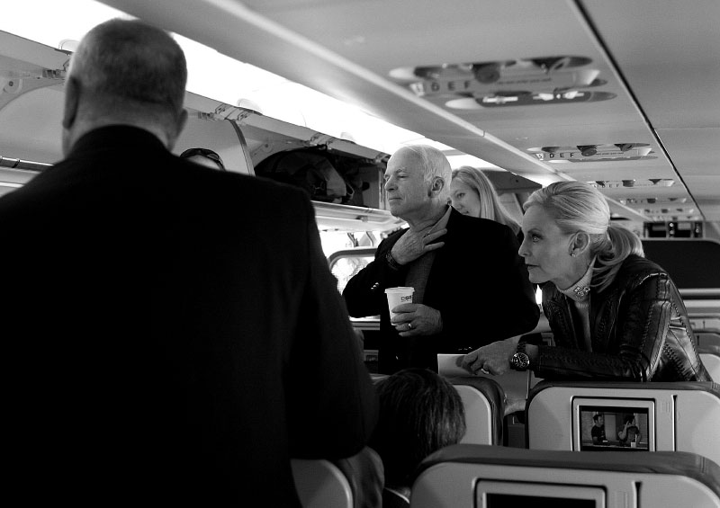 Senator John McCain and wife, Cindy, talk with staff members on the plane as he campaigns through Texas before the March primary.