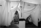 Sheets provide privacy in converted horses stalls used as makeshift exam rooms.