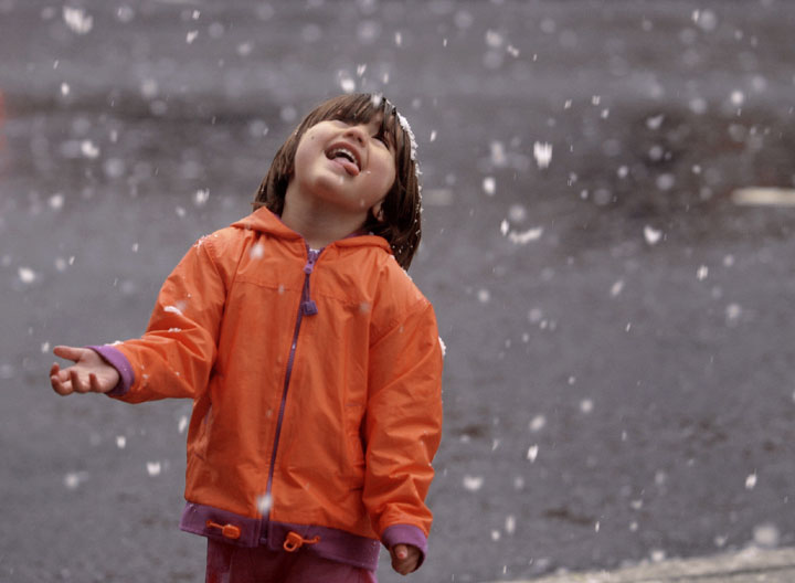 Two-year-old Baylie Herbert of Marysville gets a taste of her first snow during a rare snowstorm in downtown Marysville.