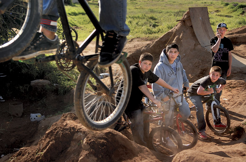 BMX riders look on as a fellow rider does a trick off a jump at an impromptu track in Olivehurst.