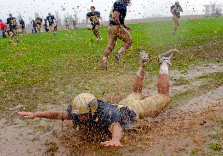 A Yuba College football player slides though the mud following the 49ers' 46-0 win over visiting Marin College.
