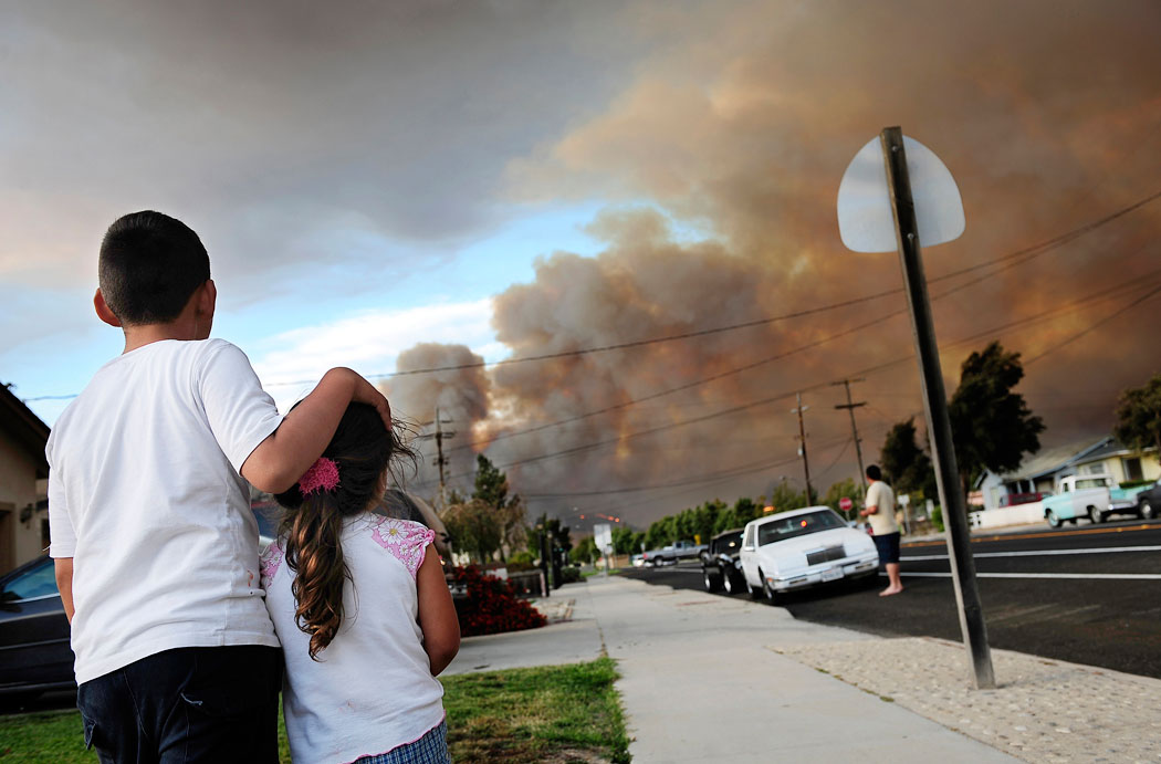 Emilio Diaz Jr., 8, of Soledad holds his 4-year-old sister, Kiria, as they watch wildfires burn through the hills in east Soledad from their home along the 300 block of East Street. According to CAL FIRE Cpt. James Dellamonica, the Gloria Fire in Soledad was caused by agricultural fireworks, a type of sparkler used to scare birds and ground squirrels.