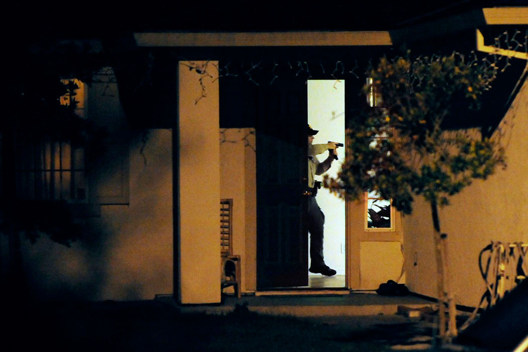 A deputy with the sheriff's department searches a house along Esperanza Circle after 35-year-old Juan Palo Lopez Ruiz of Watsonville was shot and killed and another man seriously injured during an incident Sunday night at Vista de Tierra Circle in Castroville.