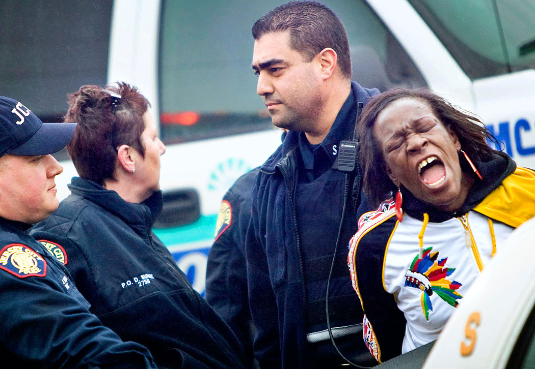 Jersey City police officers detain a distressed Irene Williams outside the scene of a shooting where three teenagers were shot at Triangle Park in Jersey City. Williams would not calm down and was trying to walk onto an active crime scene because she was afraid her niece was one of the victims. Police on the scene sent Williams to Jersey City Medical Center where she was later released.