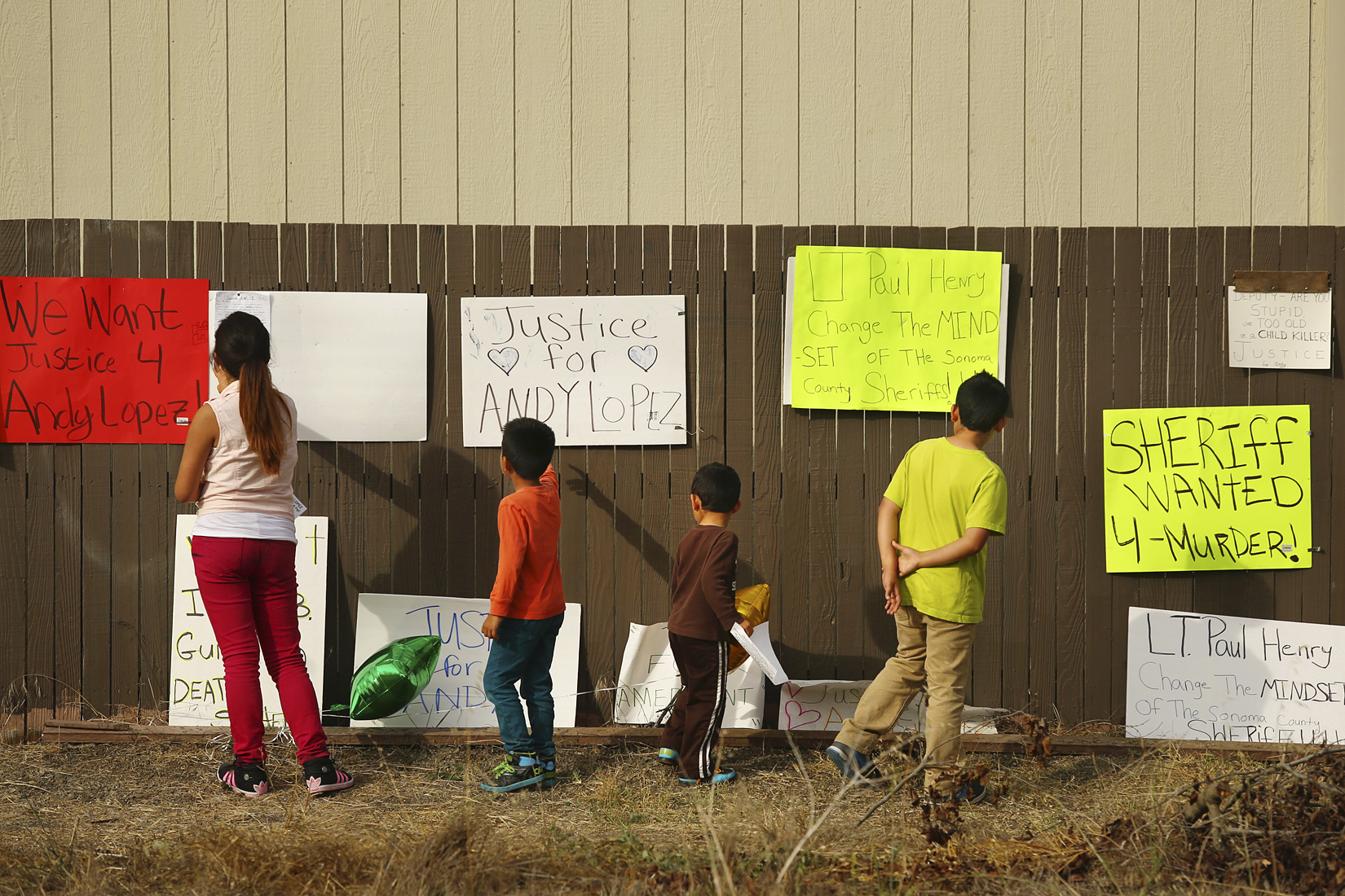 Gaby Camacho, left, and her three younger brothers, from the left, Angel, Julio and Israel read over the signs posted on the fence near the site 13-year-old Andy Lopez was shot and killed by a Sonoma County Sheriff's deputy in Santa Rosa on Friday, October 25, 2013. (Conner Jay/The Press Democrat)