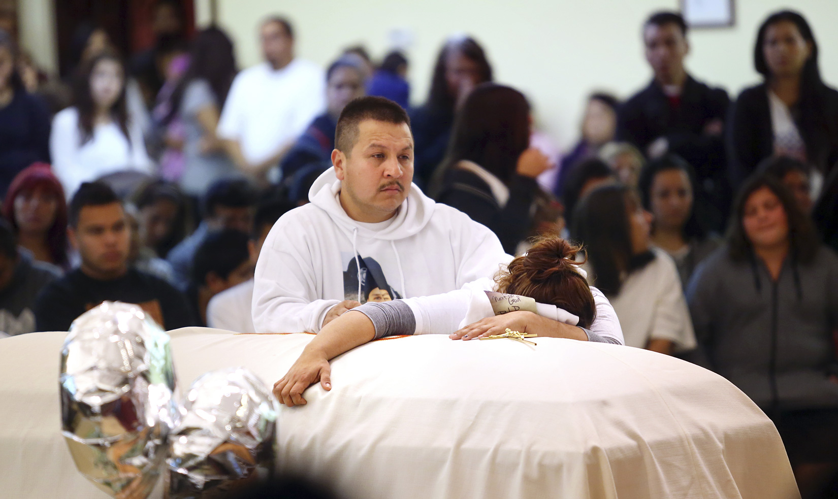 Sujey Lopez clutches the coffin holding her 13-year-old son as he husband Rodrigo Lopez consoles her during Andy Lopez's funeral ceremony funeral ceremony at Resurrection Parish in Santa Rosa on Tuesday, October 29, 2013. (Conner Jay/The Press Democrat)