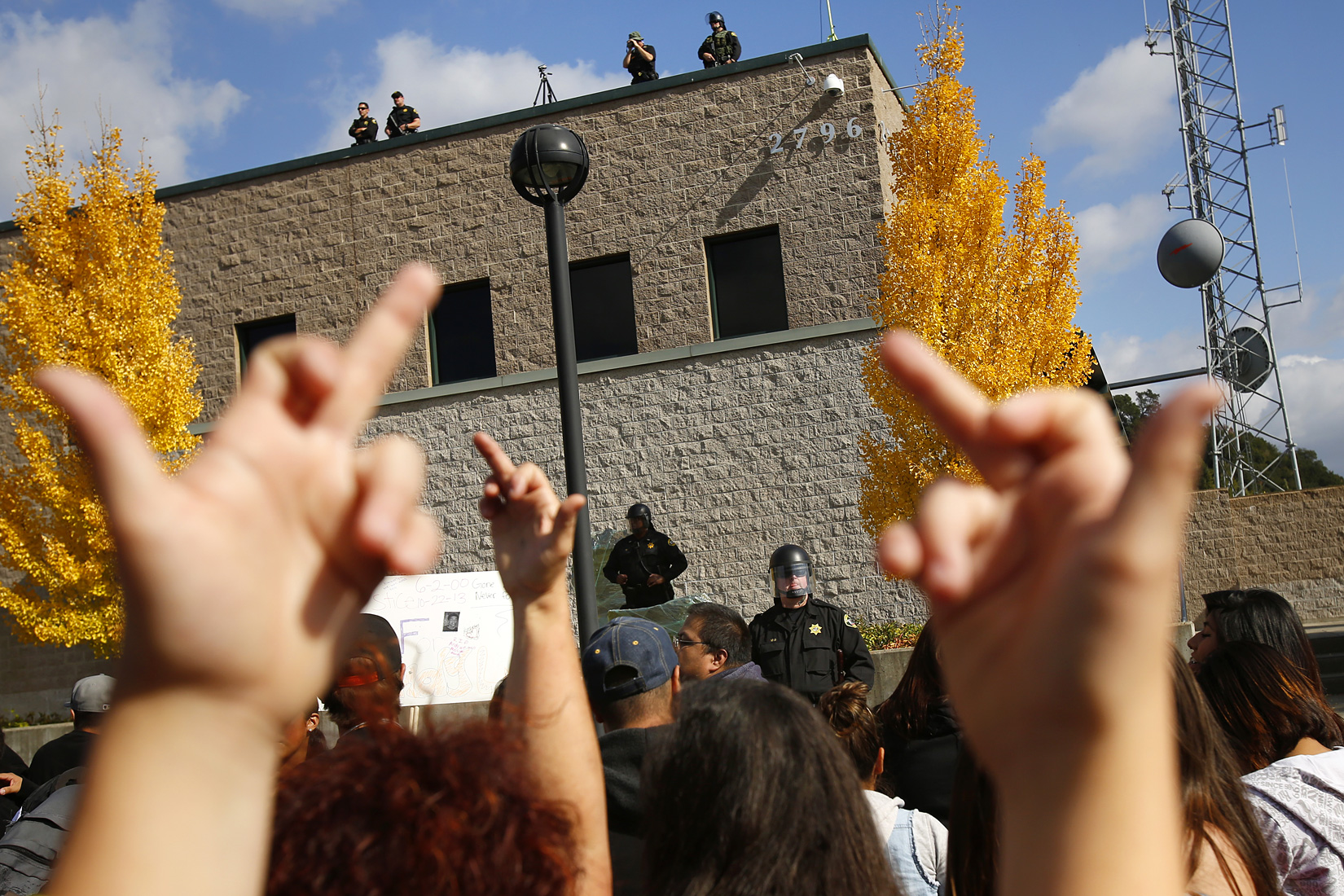 Protestors flip off Sonoma County Sheriff's deputies protecting their offices during a march in reaction to the death of 13-year-old Andy Lopez in Santa Rosa on Tuesday, October 29, 2013. (Conner Jay/The Press Democrat)