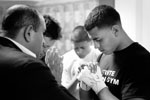 Eric Prado, right, prays with family before his fight in the Central Coast Throwdown at Palma High School.