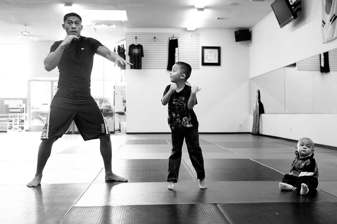 "Andre Olivas, 4, center, mimics his father Adrian Olivas' shadowing boxing during a training sessaion at the Kugtar MMA Academy in Salinas. Owner of the Kugtar MMA Academy, Vince Vanderlipe, better known as ""Master V,{quote} has operated several MMA gyms in Salinas for the past 15 years, but the options for his young fighters were limited without sanctioned fights. Those who wanted to start competing would either have to leave the state or participate in illegal fights."