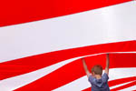 Eamon Malley, 7, of Salinas tries to hold up the large American flag covering the arena grounds at Sunday's California Rodeo Salinas.