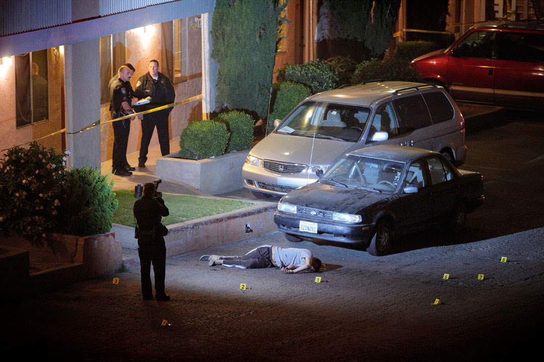 Salinas police officers and investigators mark evidence around the body of Francisco Hereida, 20, who shot and killed in the parking lot of an apartment complex Tuesday night along the 500 block of John Street night in Salinas. Hereida is the cities ninth homicide of the year and was one of four gang related shooting victims in the last five days in Monterey County.