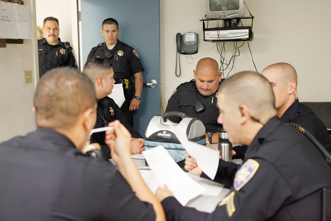 The Soledad police department listen in to their evening briefing before going out to patrol the streets September 18, 2010 in Soledad. The small police force makes combatting gangs difficult, so the the four cities of Soledad, Gonzales, Greenfield and King City have implemented the Four Cities For Peace initiative that brings officers from each city together for joint suppression operations.