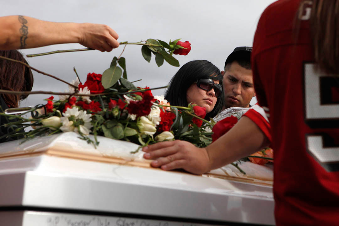 Diana Serrato, center, stands by her older brother Rogelio Serrato's coffin as friends and family lay flowers during his funeral January 13, 2011 in Greenfield. {quote}He didn't deserve this,{quote} said Diana. {quote}The sheriff killed the wrong man.{quote}