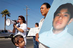 Flora Cristobal holds a picture of her 15-year-old son Rodolfo Cristobal while her daughter looks at a picture of her late brother during a peace rally August 1, 2010 in Salinas. Rodolfo was shot and killed in a gang related shooting last October 14, 2009 on Archer Street in Salinas