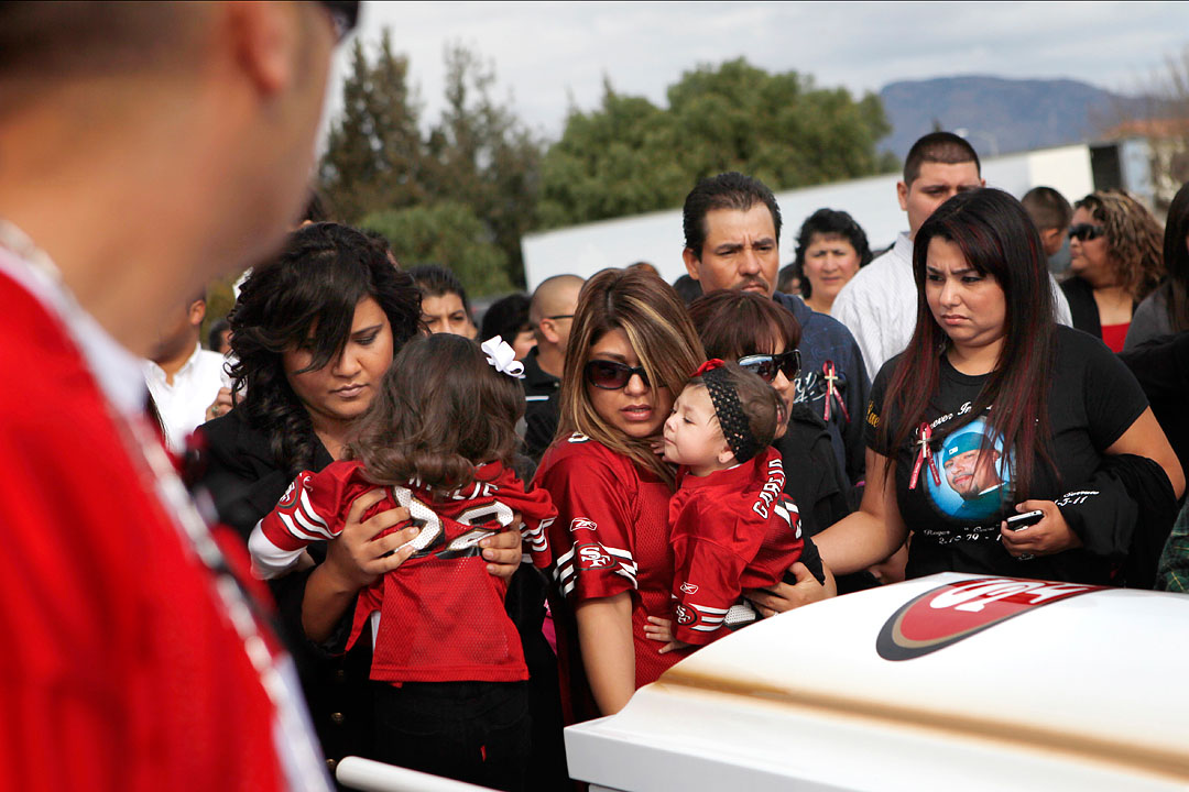 Friends of Rogelio Serrato pose their children for photo by his coffin January 13, 2011 in Greenfield. According to the Four Cities For Peace initiative, a large part of combating gangs has to do with prevention and intervention. {quote}We need to combat the image,{quote} said Soledad police Chief Eric Sills. {quote}We don't young people growing up with a picture of being in a gangster lifestyle.{quote}