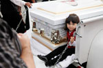 Kayla Armenta, 5, rides next to the coffin holding her uncle Rogelio Serrato during his funeral procession January 13, 2011 at Greenfield Holy Trinity Cemetery.