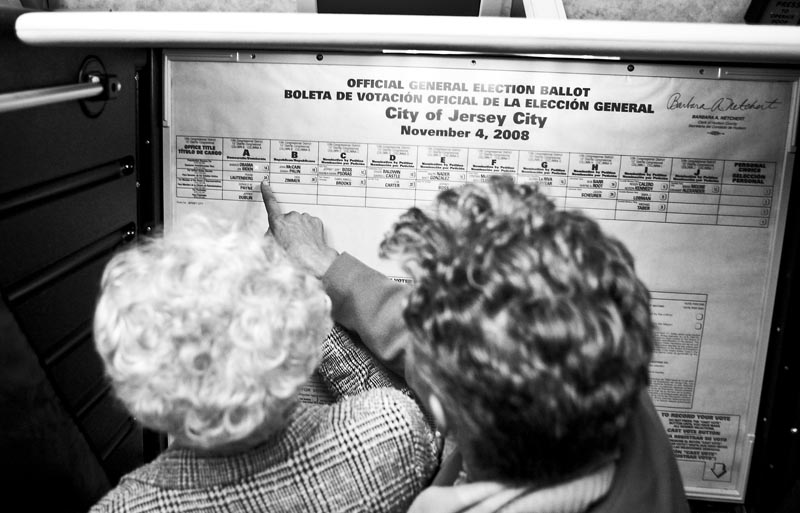 Barbara Ervin helps her mother, Grace Linkhorn, with the Jersey City voting machine, pointing out how to push the button for her candidate and register the vote. This is the first time in Linkhorn's 101-year-old life she has been able to vote for an African American candidate.