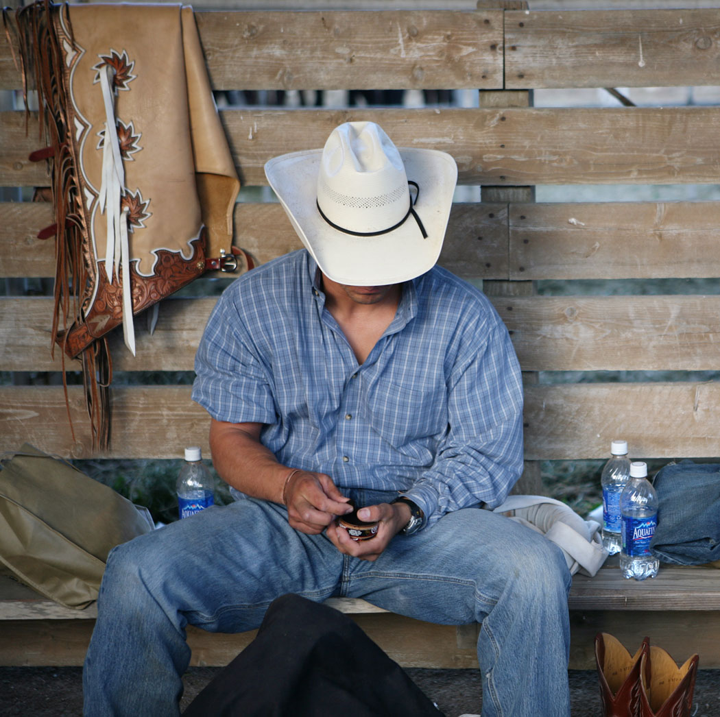 Brandon Martin of Pendleton, Oregon, rests with some chewing tobacco after competing in the bareback bronc riding during Friday's California Rodeo Salinas.