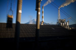 Photograph of Mount Fuji as seen through the stacks of an industrial plant in Japan.
